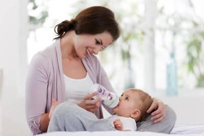 Мама кормит малыша с бутылочки