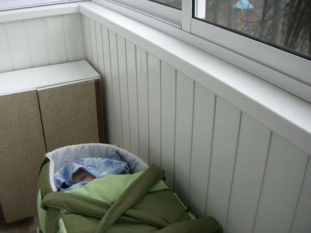 Младенец спит зимой на балконе