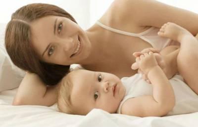 Мама и новорожденный лежат на кровати