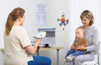 Детский офтальмолог осматривает ребенка