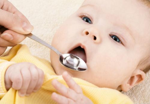Ребенку дают лекарство с ложечки
