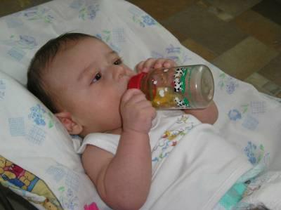 Малыш пьет чай с бутылочки