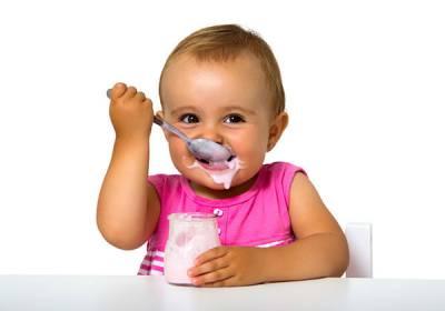 Ребенок ест йогурт ложкой