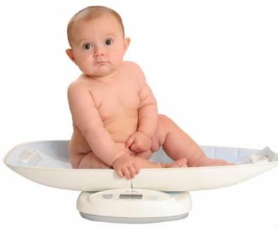 Грудной ребенок сидит на весах