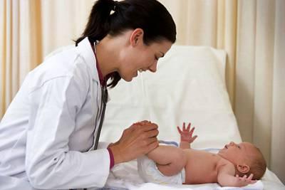 Врач осматривает грудного ребенка
