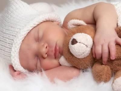 Младенец спит с игрушкой