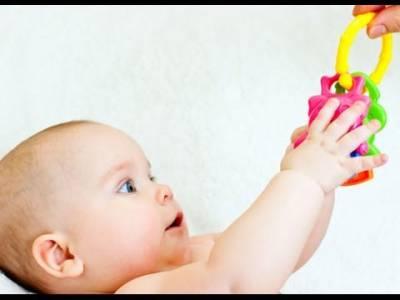 Младенец держит игрушку