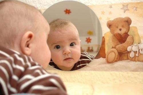 Ребенок рассматривает себя в зеркале