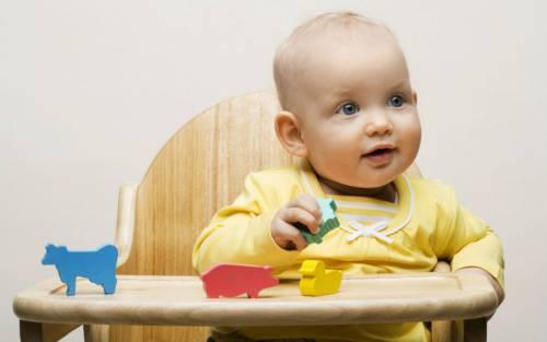 Ребенок сидит за детским столиком