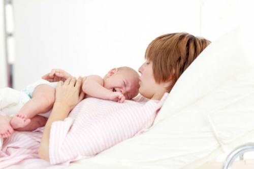 Младенец лежит на животе у мамы