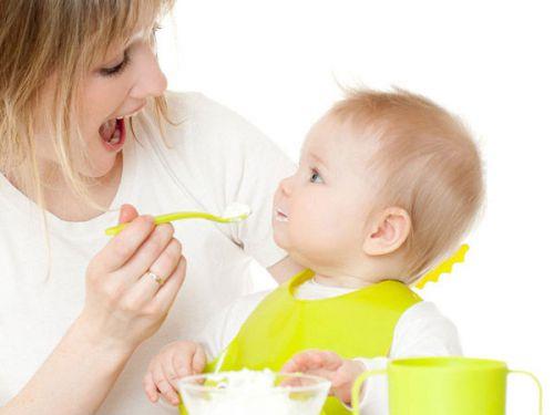 Мама кормит ребенка творогом