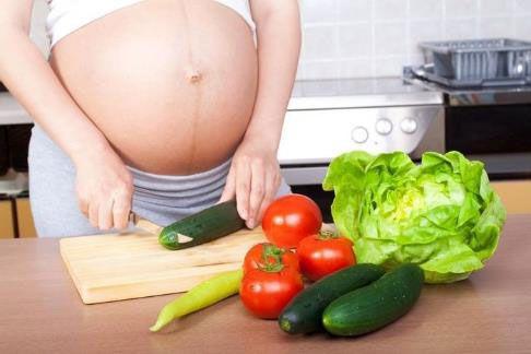 Беременная женщина режет овощи