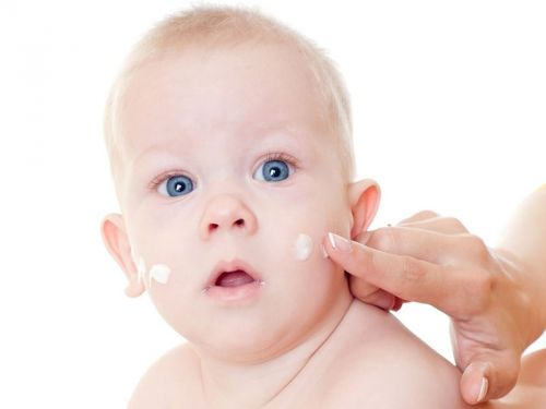 Нанесение крема на лицо младенца