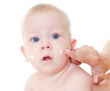 Нанесение крема на кожу младенца