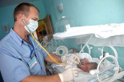 Врач обследует младенца