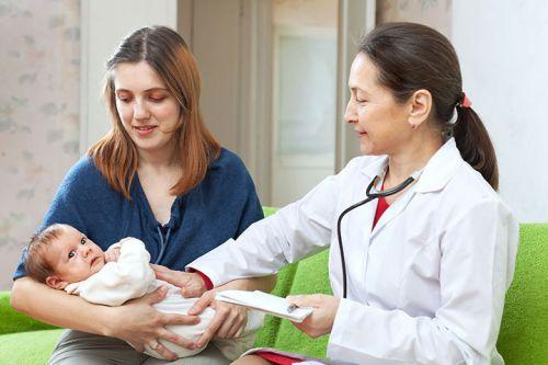 Врач осматривает новорожденного