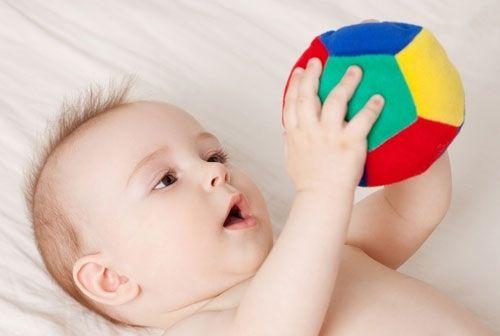Младенец играет с мячом