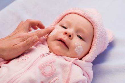 Нанесение крема на щечки ребенка
