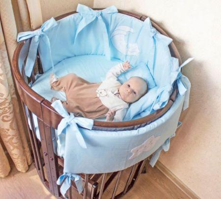 Младенец в круглой кроватке