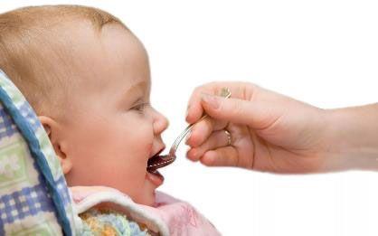 Младенец принимает лекарство с ложечки