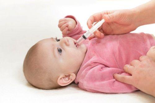 Мама дает лекарство младенцу