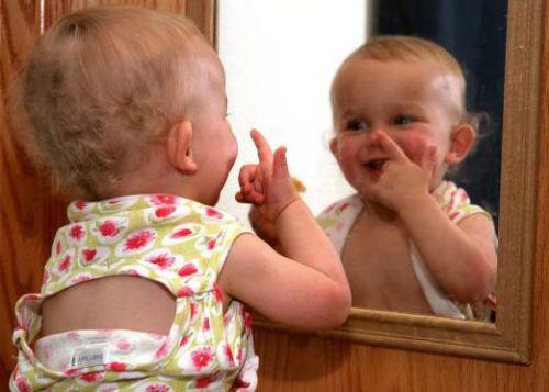 Малыш смотится в зеркало