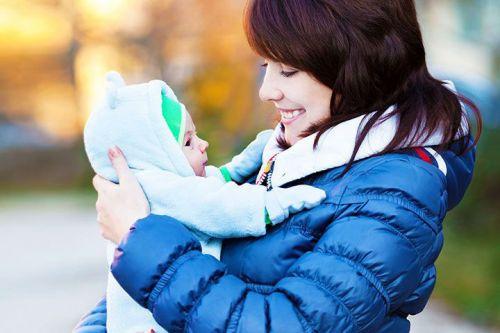 Ребенок на прогулке на руках у мамы