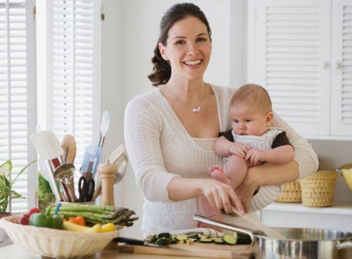 Мама с младенцем готовит обед