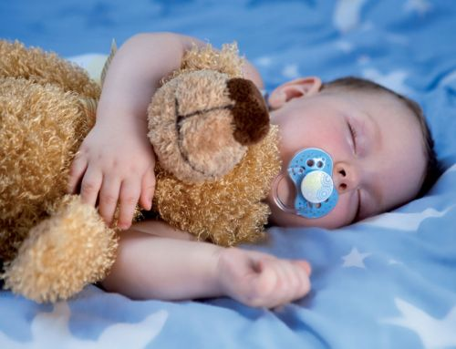Младенец спит с игрушкой и с пустышкой