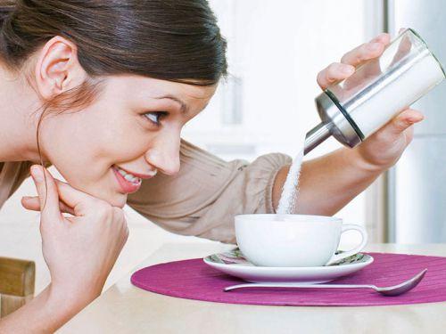 Женщина насыпает сахар в чай