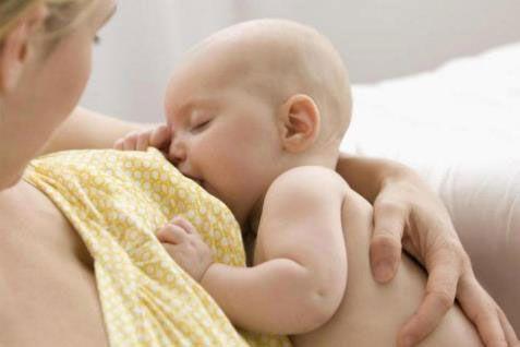 Мама кормит грудью младенца