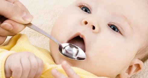 Младенцу дают лекарство в ложечке