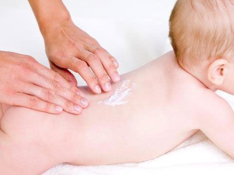 Нанесение крема на тело младенца