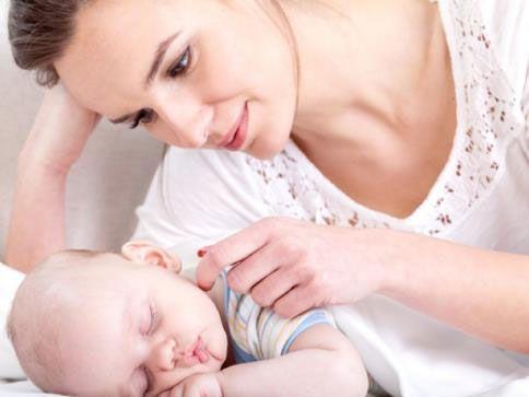 Мама рядом со спящим младенцем
