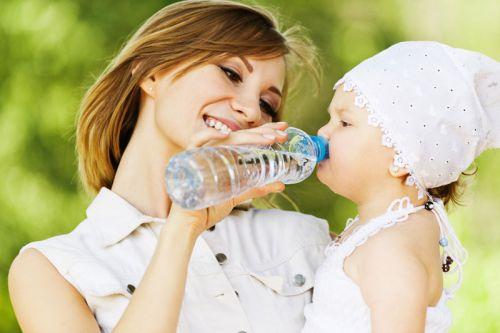 Мама поит ребенка на прогулке в жару