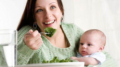 Женщина с ребенком на руках ест салат