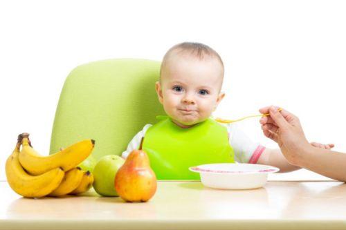 Ребенка за столом кормят из ложечки