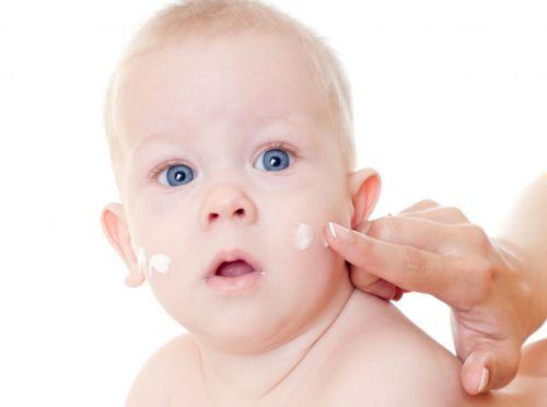 Мама мажет лицо младенца кремом