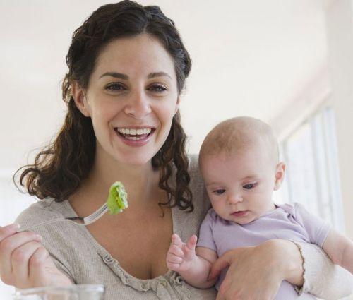 Женщина с младенцем ест салат