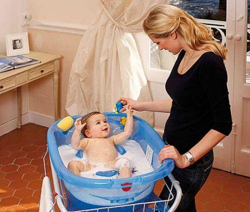 Мама купает малыша в ванночке