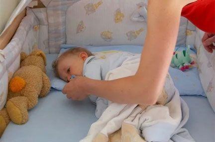 Ребенок лежит в кроватке