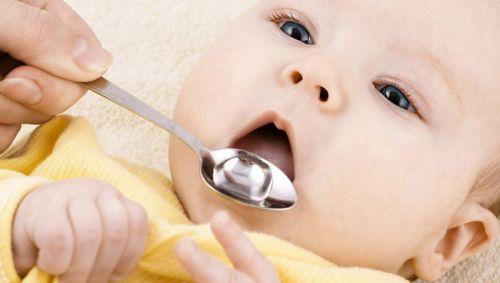 Ребенку дают лекарство в ложке