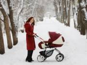 Мама гуляет с новорожденным в зимнем парке