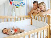 Ребенок в кроватке и родители
