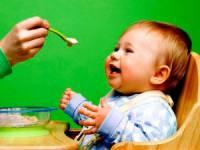 Мама кормит ребенка с ложечки