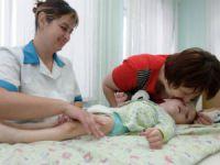 Врач осматривает новорожденного ребенка
