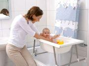 Младенца купают в ванночке на подставке