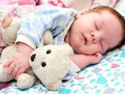 Младенец спит с игрушечным медвежонком