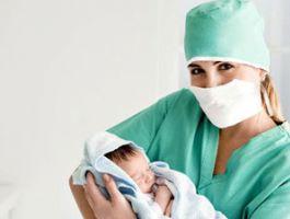Акушерка держит новорожденного