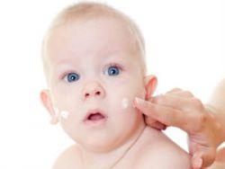 Нанесение мази на кожу младенца